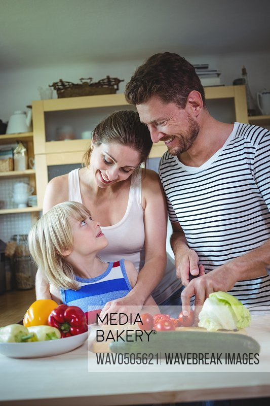 Happy family looking at each other while preparing salad in the kitchen at home