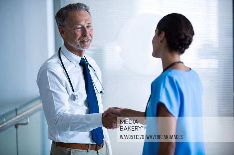 Doctor shaking hands with colleague at hospital