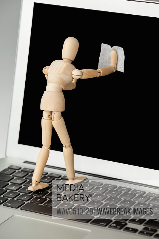 Wooden figurine cleaning the display screen of laptop with a cloth against white background