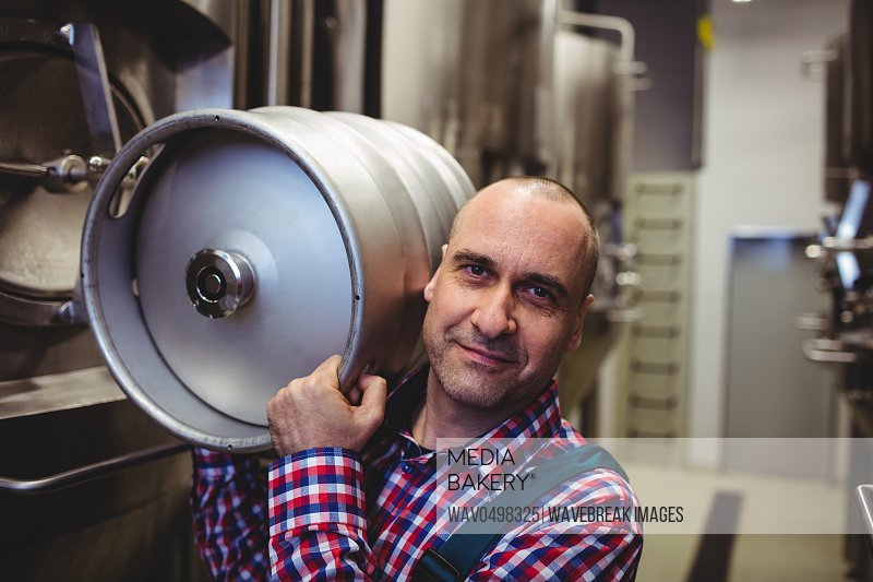 Portrait of male manufacturer carrying keg in brewery