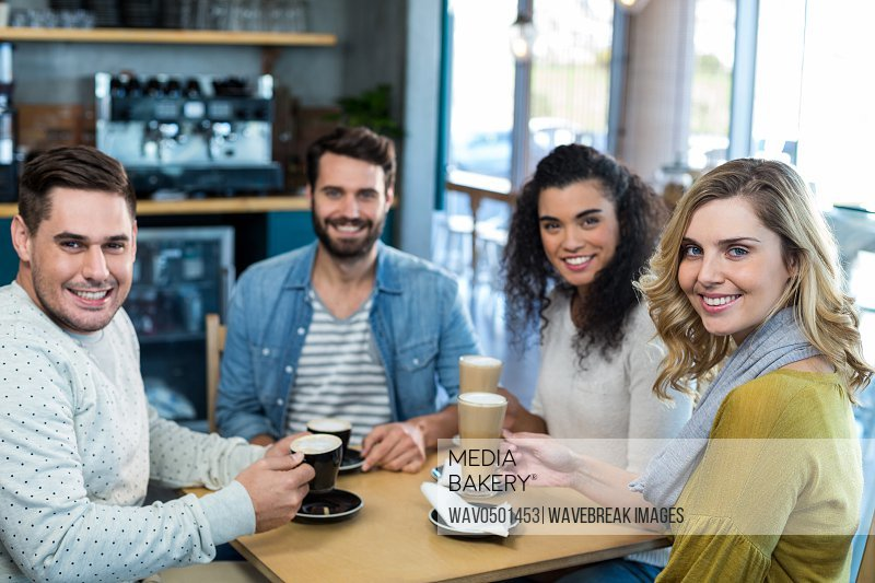 Portrait of smiling friends having a cup of coffee and cold coffee in cafA?