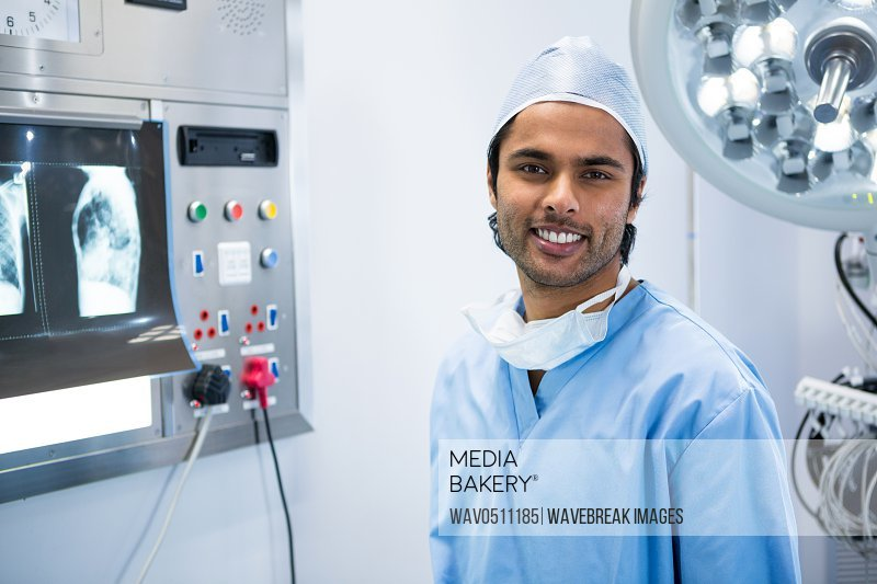 Portrait of male surgeon standing in operation theater of hospital