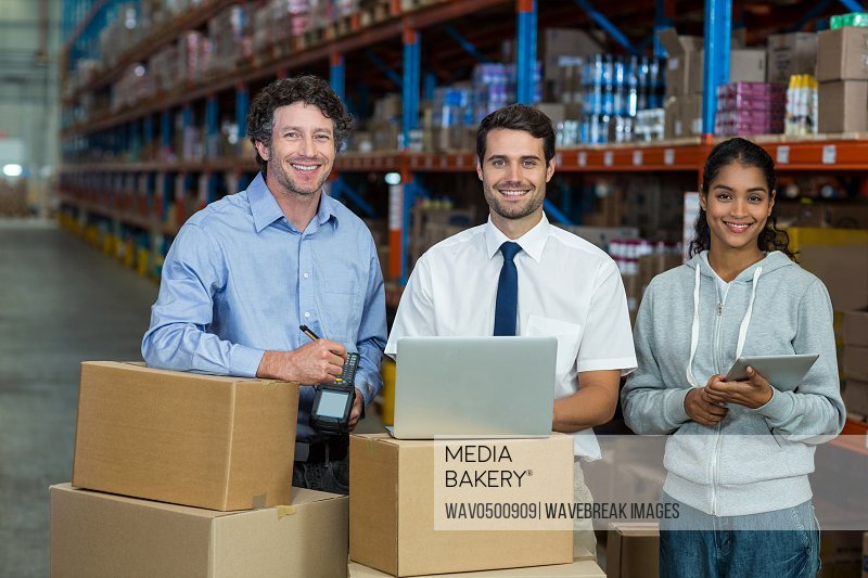 Portrait of warehouse manager and worker standing together in warehouse