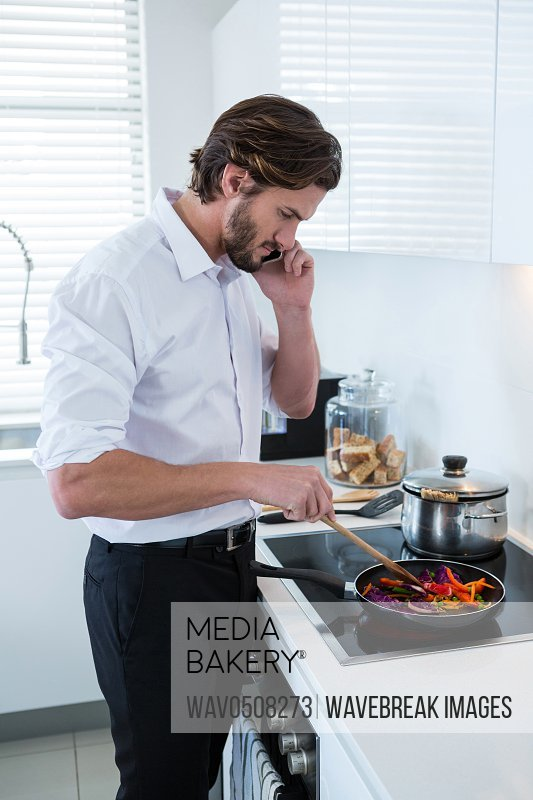 Man talking on mobile phone while preparing food in kitchen at home