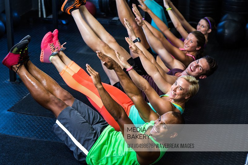 Portrait of male and female athletes in boat position at gym