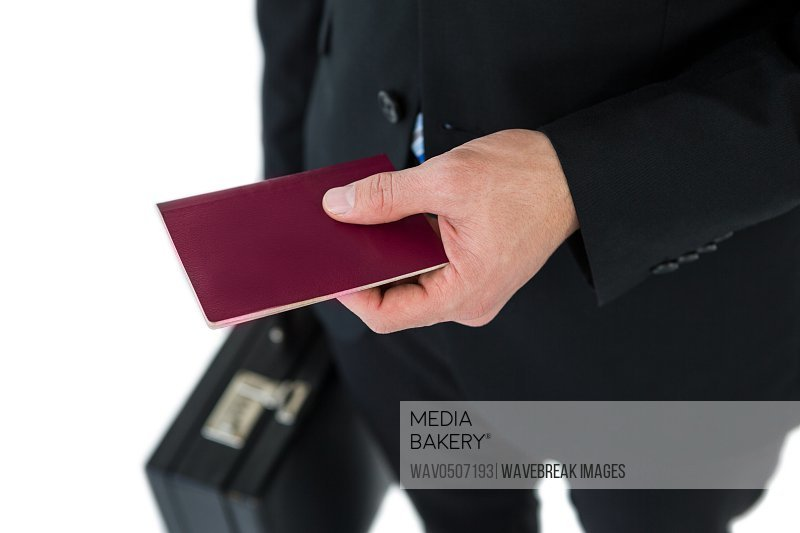 Mid section of businessman holding briefcase and passport on white background