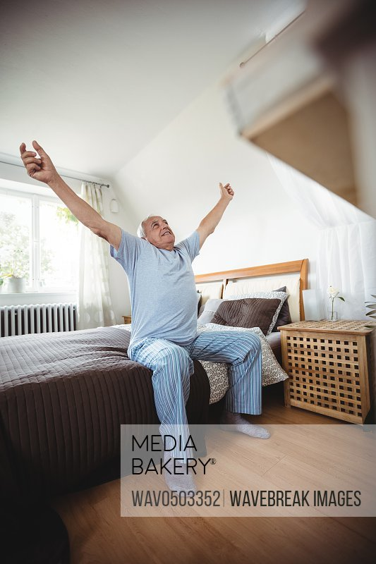 Senior man yawning on bed in bedroom