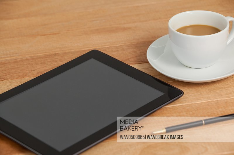 Digital tablet with pen and cup of tea on table