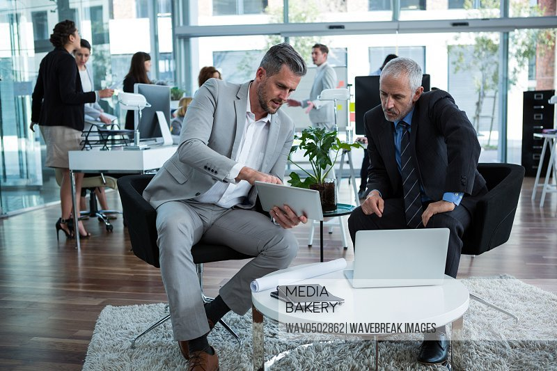Businesspeople discussing over digital tablet in office