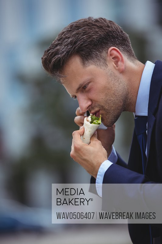 Handsome businessman eating snacks while talking on mobile phone