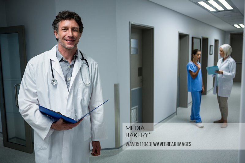 Portrait of doctor holding medical report in corridor at hospital