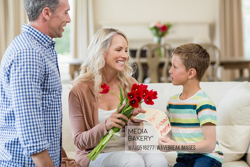 Boy giving card and roses to his mother