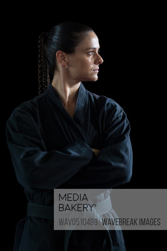Female karate player standing with arms crossed against black background