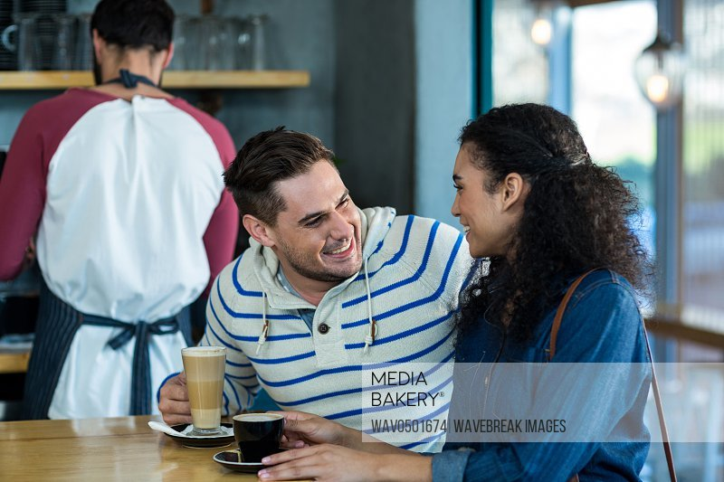 Smiling young couple interacting while having coffee in cafe