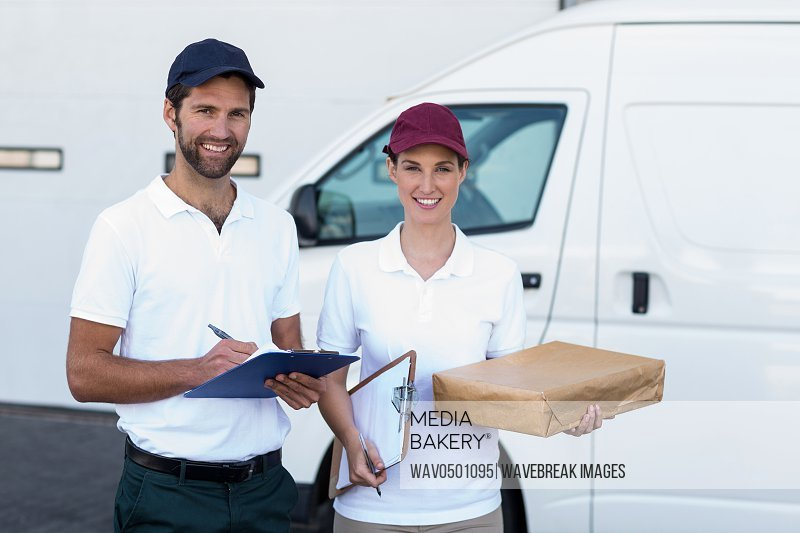 Portrait of delivery man and woman standing with clipboard and parcel outside the warehouse
