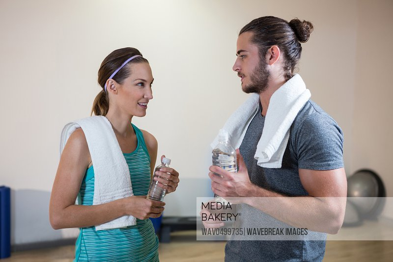 Fitness trainer and woman holding water bottle in fitness studio