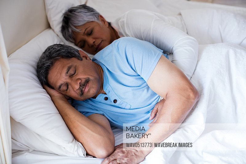 Senior couple sleeping together on bed in bedroom
