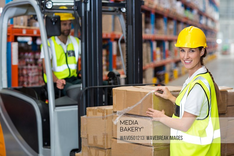 Portrait of female worker smiling in warehouse