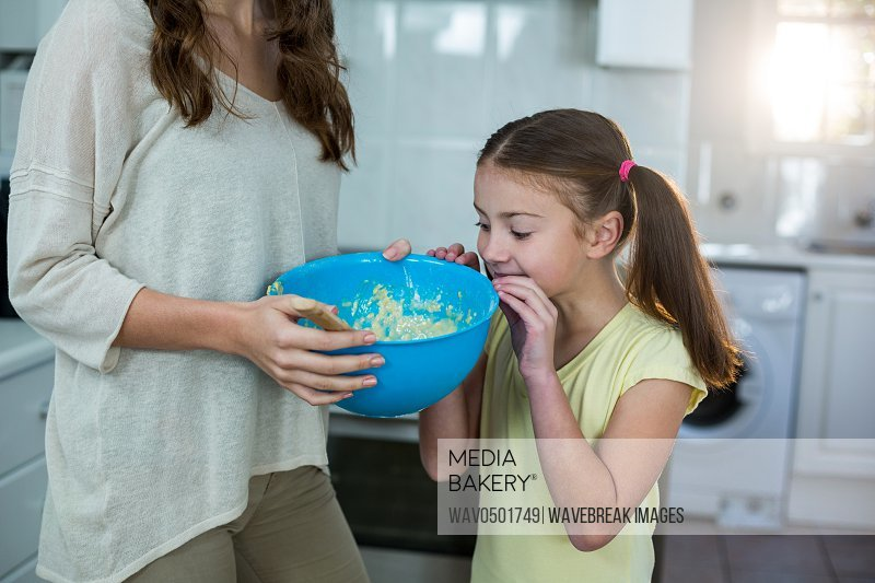 Mother and daughter with bowl of breakfast in kitchen
