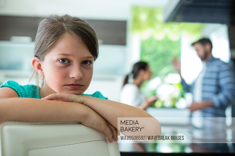 Portrait of sad girl leaning on chair while parents arguing in background at home