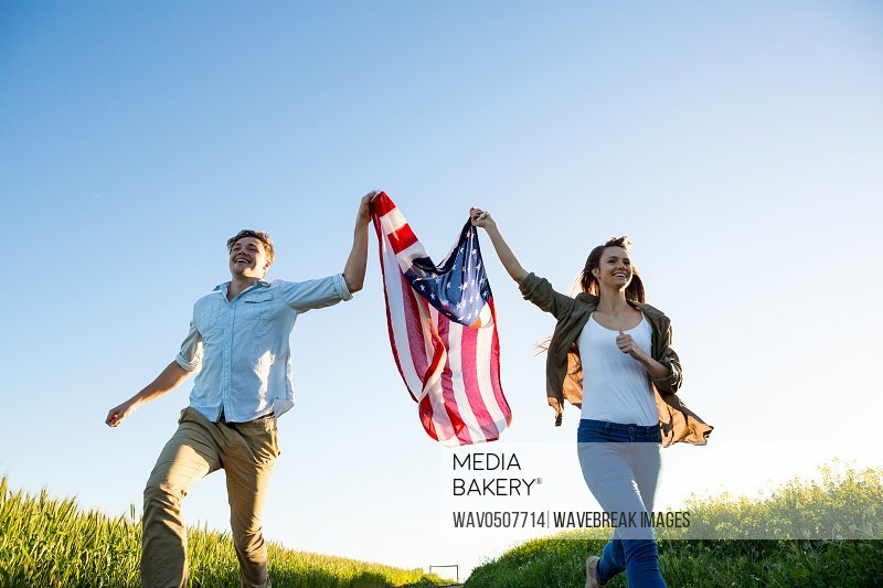 Couple holding amrican flag and running in field on a sunny day