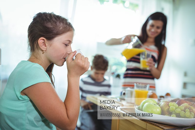 Girl drinking cup of tea with family having breakfast at home