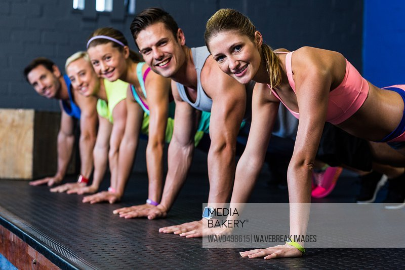 Portrait of happy male and female athletes doing push-ups in gym