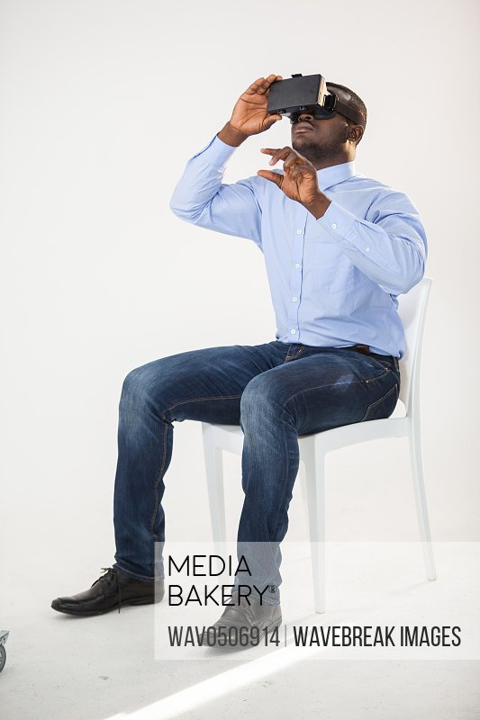 Man sitting on chair and using virtual reality headset against white background