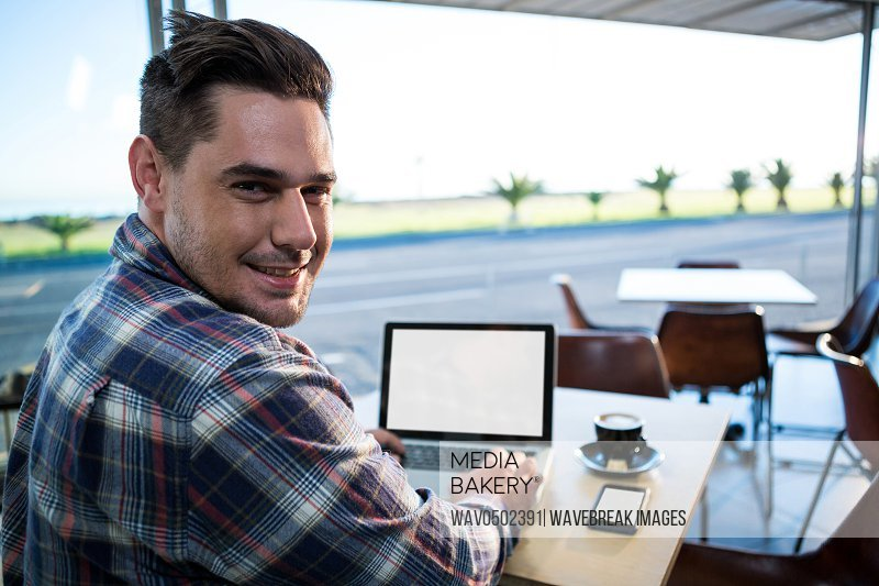 Portrait of smiling man using his laptop in coffee shop