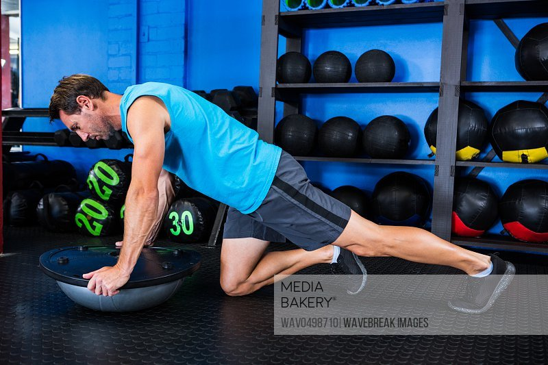 Young man using BOSU ball while exercising in gym