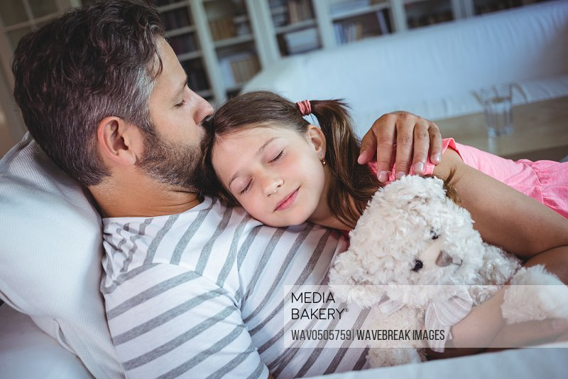 Daughter sleeping in her fathers arms at home