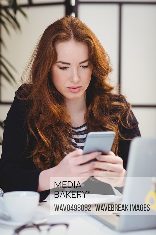 Beautiful young female executive using mobile phone at creative office