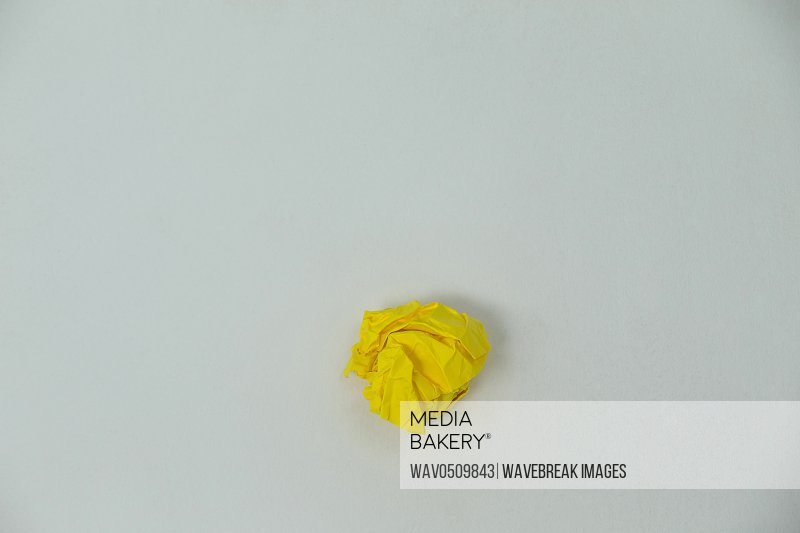 Close-up of yellow crumpled paper ball on a white background