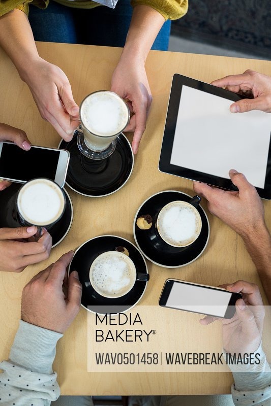 Friends using mobile phone and digital tablet while having cup of coffee in cafA?