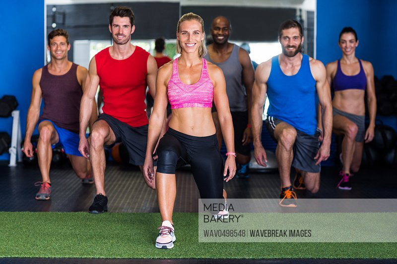 Portrait of smiling athletes exercising in gym