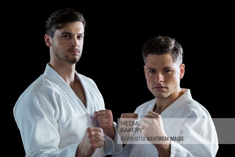 Portrait of Two karate fighters performing karate stance against black background