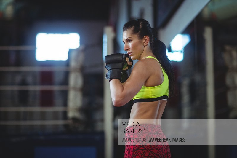 Female boxer performing boxing stance in fitness studio