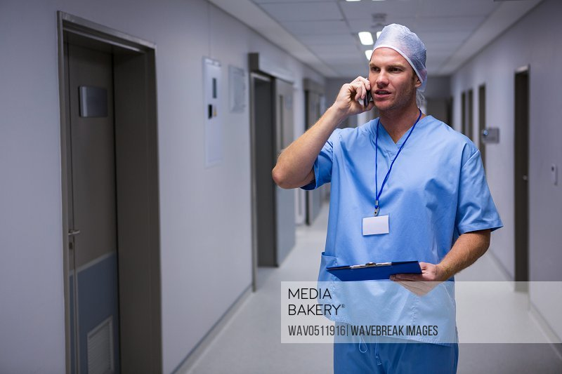 Surgeon standing in corridor and talking on mobile phone in hospital