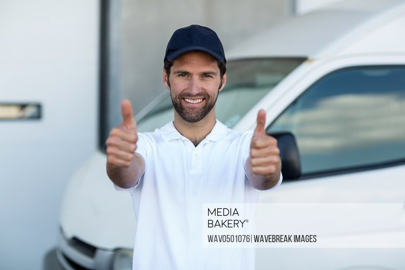 Portrait of delivery man showing thumbs up in front of van