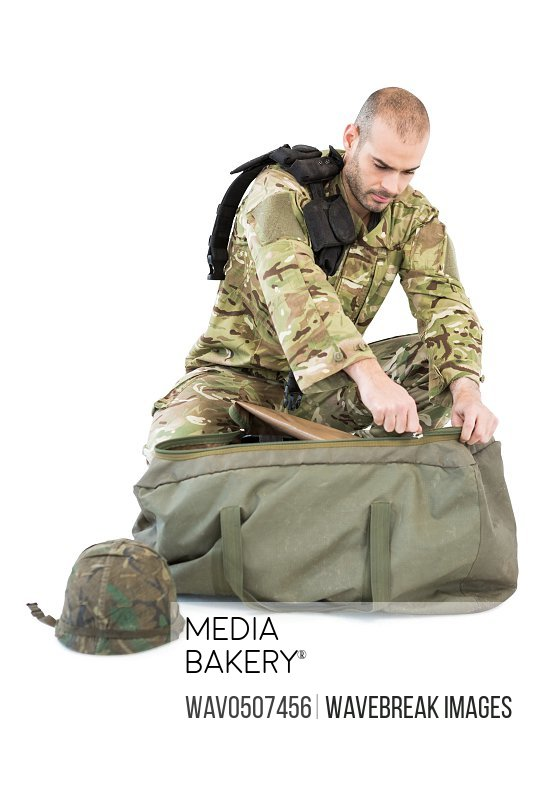 Solider packing his bag against white background