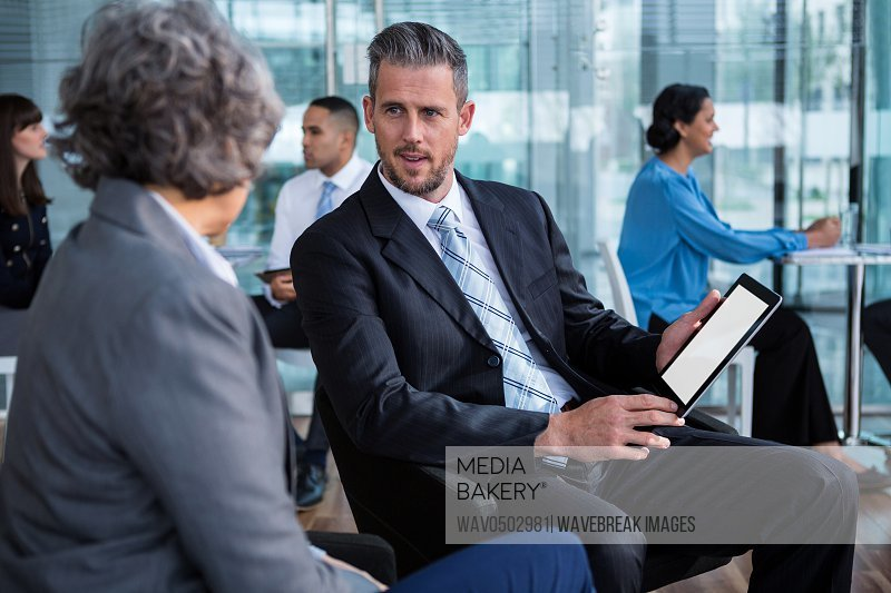 Businesspeople having discussion over digital tablet in office