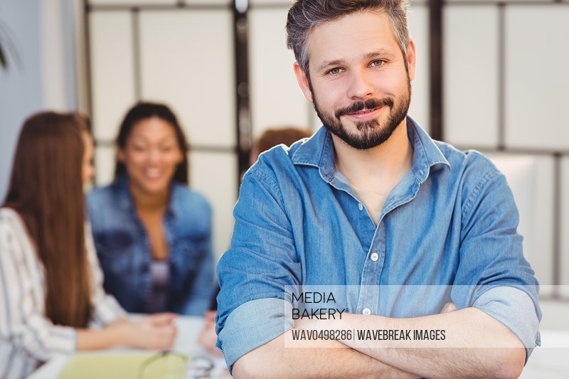 Portrait of smiling businessman with arms crossed against female coworkers in meeting room