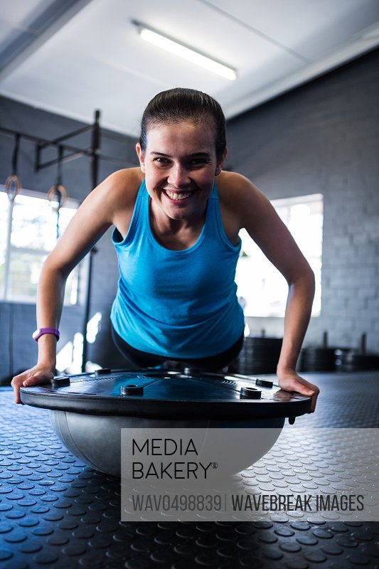 Portrait of smiling athlete with BOSU ball while exercising in gym