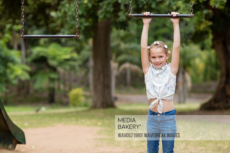 Girl hanging on a playing equipment in park