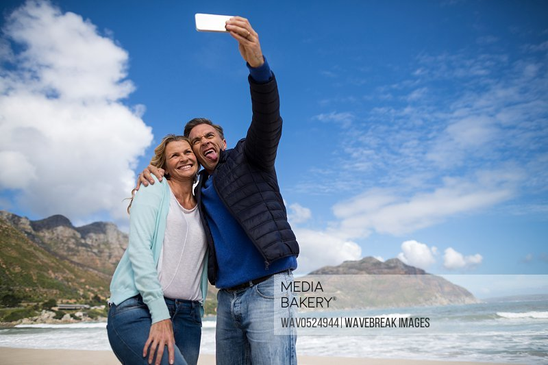 Mature couple sticking out tongue while taking selfie