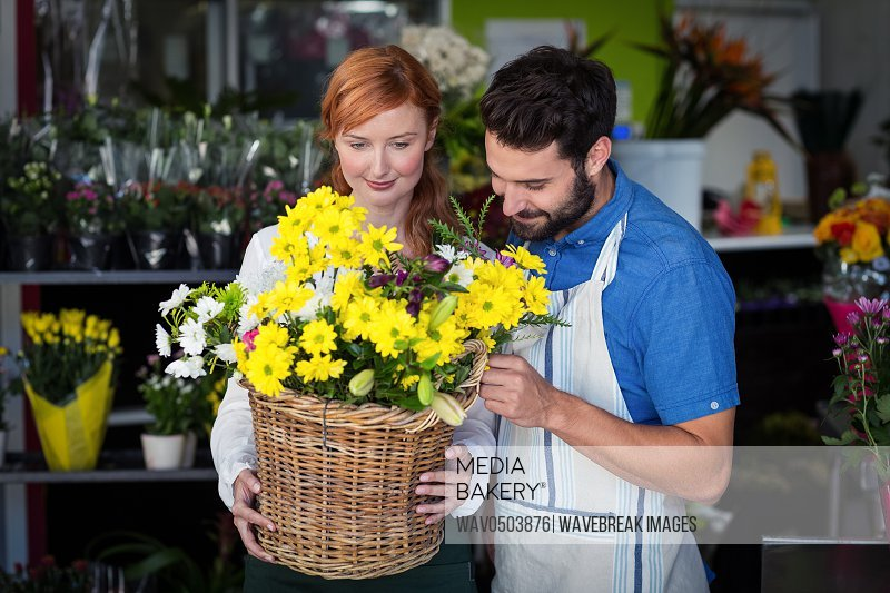 Couple standing with flower basket in the flower shop