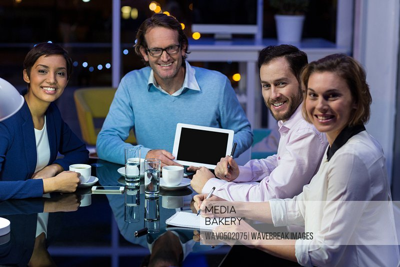 Businessman discussing work on digital tablet with colleagues in office at night