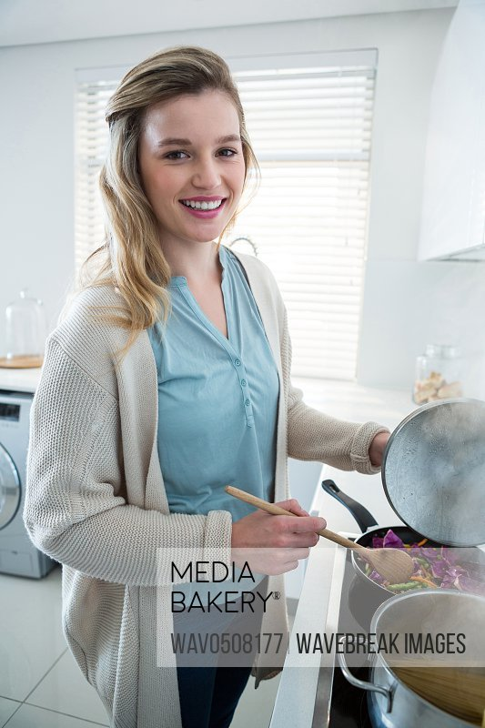Portrait of woman cooking food in kitchen at home