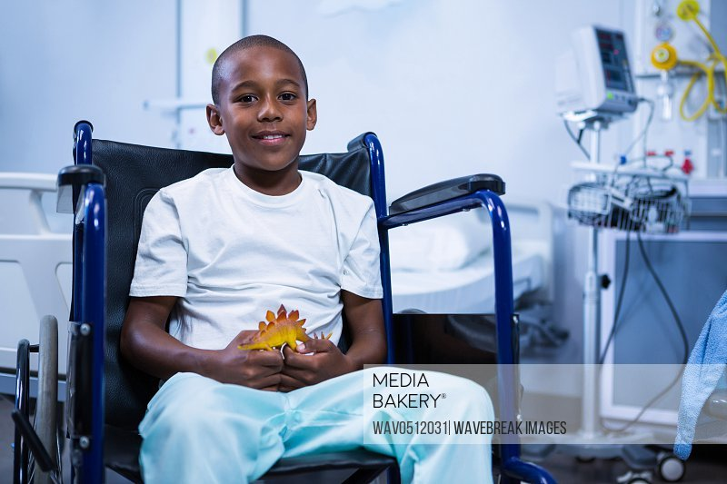 Portrait of boy sitting on wheelchair with toy in ward at hospital