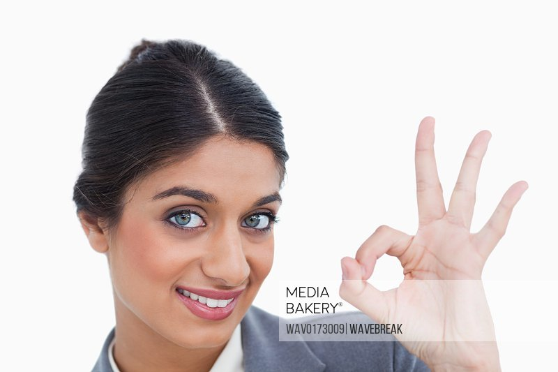Smiling female entrepreneur giving her approval against a white background